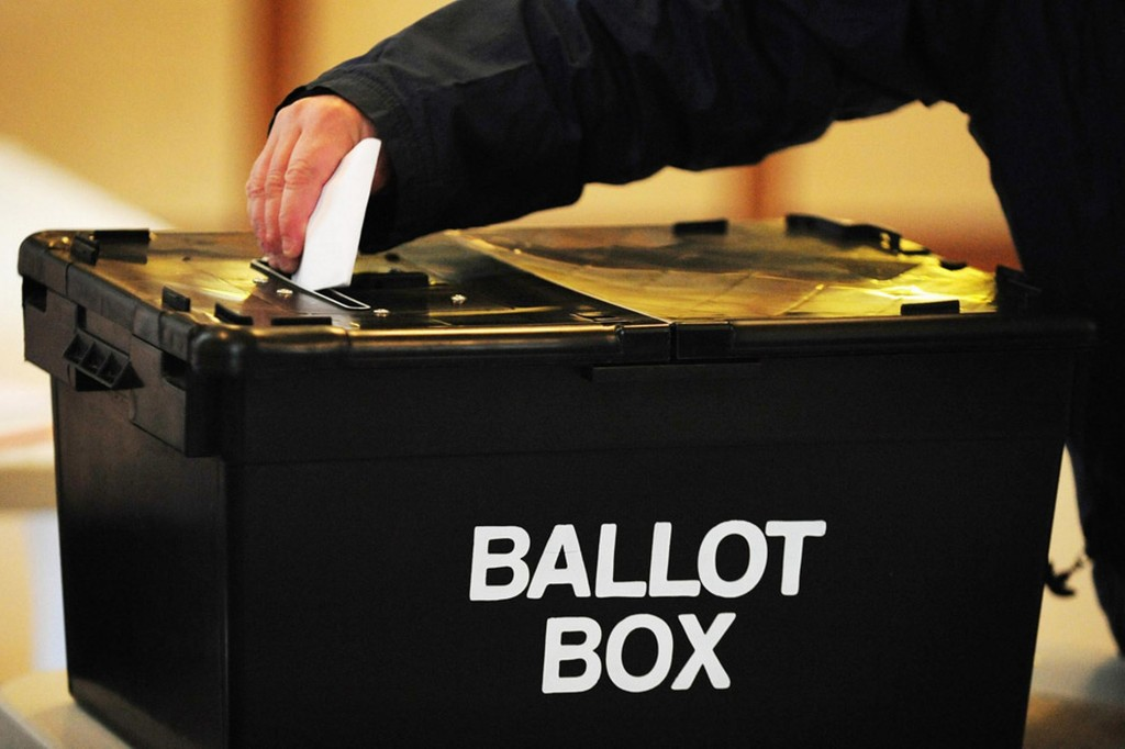 A voter placing a ballot paper in the ballot box at the polling station at Market Hall in Swadlincote, Derbyshire