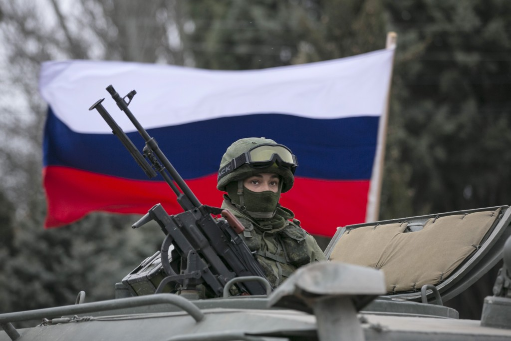 A pro-Russian man holds a Russian flag behind an armed servicemen on top of a Russian army vehicle outside a Ukrainian border guard post in the Crimean town of Balaclava